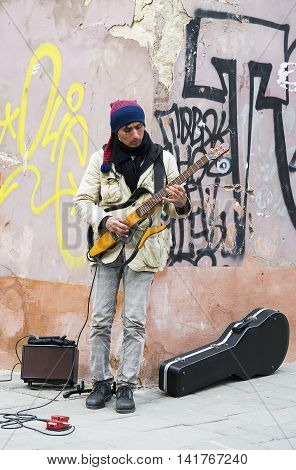 Lviv Ukraine - April 14 2015: Man playing guitar for citizens in the old quarter of the city of Lviv Ukraine.