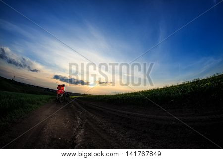 Man on mountain bike rides on the trail on a beautiful sunset. Wide view