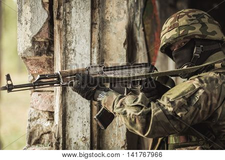 Camouflaged soldier in helmet standing close to the hole in the wall with a weapon
