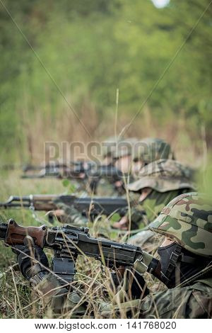 Soldiers in helmets laying on a training ground with the weapon and the forest behind them