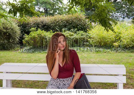 Young beautiful girl sit on a banch and call