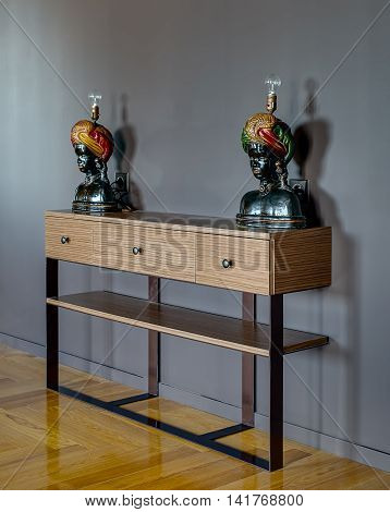 Wooden rack with three drawers on the gray wall background. On the rack there are two lamps in a form of black female sculpture. On the floor there is a parquet. Indoors. Vertical.