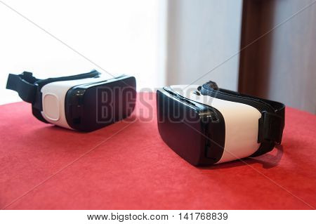 Couple of virtual reality headsets laying on the table prepared to be used. Advanced computer technology and VR experience concept.