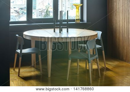Wooden round table with three chairs on the background of the window with yellow vase and dark wall. Wooden wall is on the right. On the floor there is a parquet. On the table there is a candlestick.