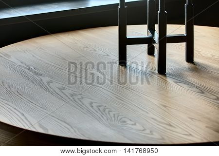Close-up photo of the wooden table. There is a black candlestick on it. Indoors. Horizontal.