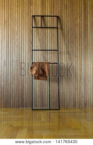 Black metal frame stand which leans on the wooden wall. Brown pullover hangs on the stand. On the floor there is a parquet. Indoors. Vertical.