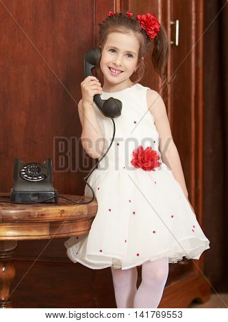 Cute little girl stands beside the round oak table. Girl holding the ear up the old phone