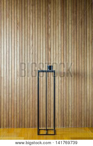 Black metal stand on the background of the wooden wall. There is a dark glass box on the stand. On the floor there is a parquet. Indoors. Vertical.