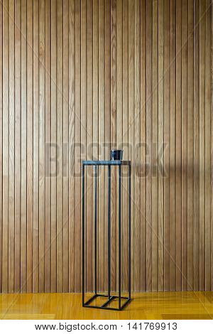 Dark metal stand on the background of the wooden wall. There is a dark glass box on the stand. On the floor there is a parquet. Indoors. Vertical.