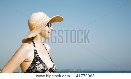 A woman is standing on the beach with her fancy hat and sunglasses. Fedora hat and sunglasses helps to prevent direct contact of eye and the sun.