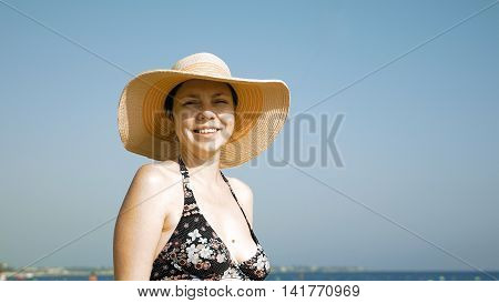 A woman is standing on the beach with her fancy jute hat. Fedora hat helps to prevent direct contact of eye and the sun.