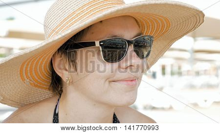 A woman is shown at the beach with style attire. One can still be fashionable and in trend while traveling. A nice pair of sunglasses completes the look.