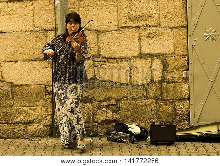 Lviv Ukraine - July 12 2014: The woman plays the violin for the citizens in the old quarter of the city Lviv Ukraine.