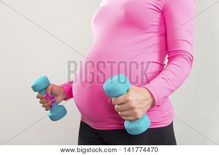 Pregnant woman exercising strength with dumbbells weights. Lifts two weights with a swollen belly.