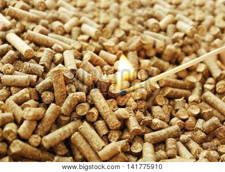 human hand holding burning match on solid pellets background