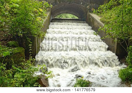 The waterfall is a torrent pouring from the top from under the bridge.
