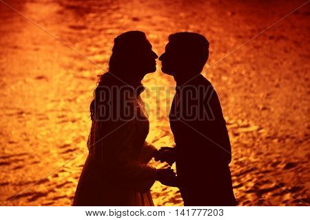 Lovers on the sunset. The kiss of lovers on a background of the sea. The red sunset. The romance of love. Backlight shot of a pair of lovers. Honeymoon at sea.