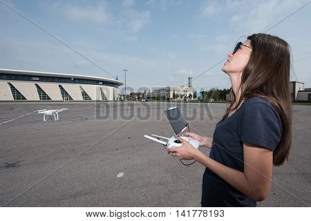 Saint-Petersburg Russia - July 23 2016: A young woman in sunglasses raises drone in the sky on a deserted town square.