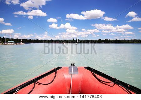 Red colored rubber motor boat floating to harbour haven