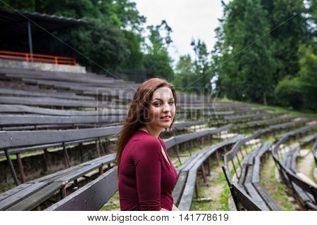 Young beautiful girl sit on a banch