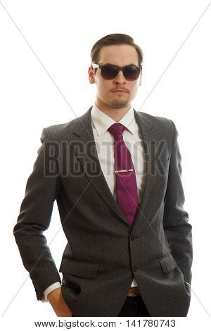 A young adult in a fancy suit with sunglasses