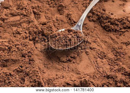 Cocoa powder into a spoon over a cocoa
