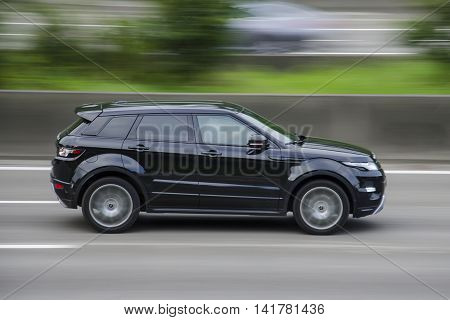 Land Rover Range Evoque on the highway with blurred background.
