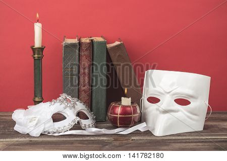 Theater concept. Closeup of white classical carnival masks with vintage books burning candles in candlesticks on red background.
