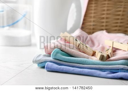 Clean clothes with pins on table
