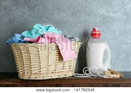 Clothes in wicker basket and detergent on table