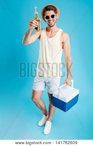 Full length of smiling young man holding cooler bag and drinking beer over blue background