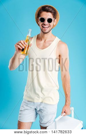 Happy handsome young man with cooler bag standing and drinking beer over blue background