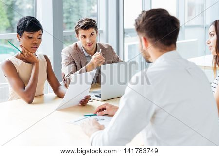 Group of young businesspeople working with laptop at meeting in office