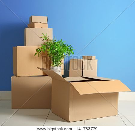 House move concept. Carton boxes on blue wall background
