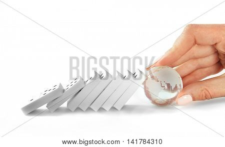 Woman hand with transparent ball of earth stops falling dominoes