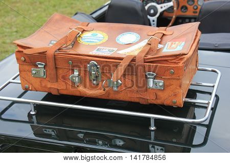 Vintage leather suitcase on a sports car