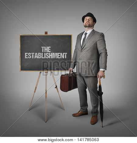 The establishment text on  blackboard with businessman holding umbrella and suitcase