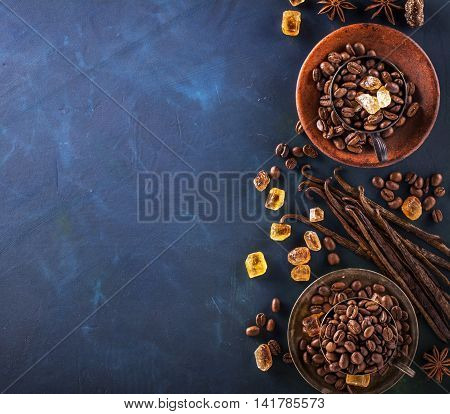 Coffee beans, chocolate drops, vanilla pods, cinnamon sticks, anise stars and brown sugar in a vintage silver cups on a dark textural wooden background. selective Focus