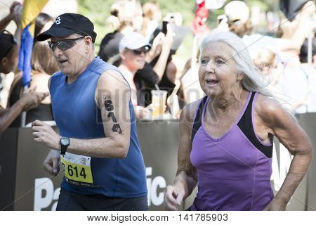 NEW YORK CITY - JULY 24 2016: Athletes approach the finish line of the NYC Triathlon Race in Central Park. The run is 10 kilometers and the race is the only International Distance triathlon in the city.