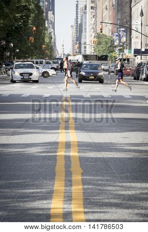 NEW YORK CITY -  JULY 24 2016: Athletes running in the NYC Triathlon Race on West 72nd St cross over Central Park West. The run is 10k and the race is the only International Distance triathlon in the city.