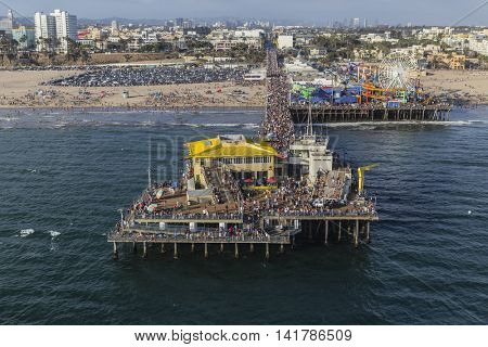 Santa Monica, California, USA - August 6, 2016:  Aerial of large crowds of summer tourists on popular Santa Monica Pier near Los Angeles.