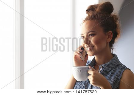 Portrait of beautiful African American girl with coffee and cellphone