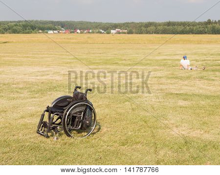 The Moscow region - 15 July 2016: Black wheelchair standing in a field on festevale