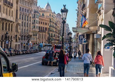 Barcelona Spain - June 19 2016: Pedestrians walk along one of the busiest streets Via Laietana filled with hotels and restaurants in the city Barcelona Spain.