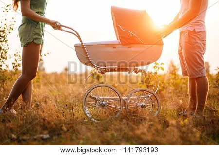 love, parenthood, family, season and people concept - smiling couple with baby pram in autumn park.