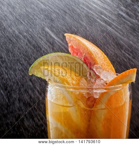 Chilled soft drinks with ice, citrus fruits and berries, black background, selective focus.