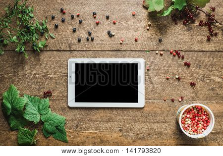 Workspace. Composition with tablet pc and bilberries, red currant with leaves in the old wooden impressive boards. Natural light shadows.