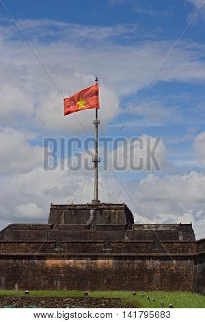 Impressive view on the flag tower in the Citadel of Hue Imperial City Central Vietnam Asia. The flagpole with huge red flag with yellow star is surrounded by water moat with green water lilies.