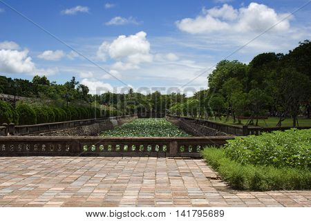 Gardens in Citadel Hue Central Vietnam. Sunny picture with blue sky and few clouds. Water lilies in the riverbed.