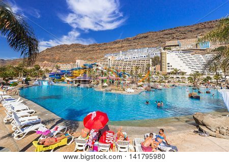 TAURITO, GRAN CANARIA, SPAIN - APRIL 20, 2016: Tourists on sun holidays at the Lago Taurito aquapark in Taurito, Gran Canaria. Taurito is very popular tourist destination